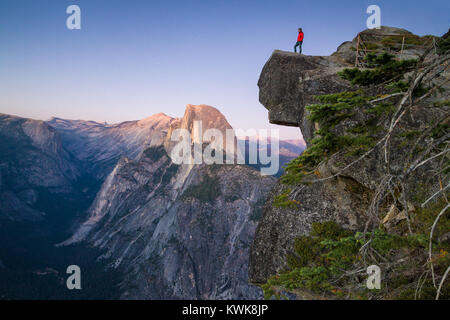 A fearless hiker is standing on an overhanging rock looking towards famous Half Dome at Glacier Point at sunset, - Stock Photo