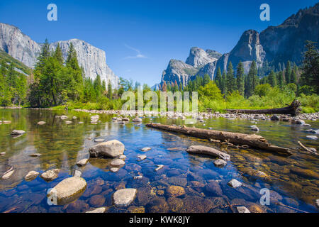 Classic view of scenic Yosemite Valley with famous El Capitan rock climbing summit and idyllic Merced river on a - Stock Photo