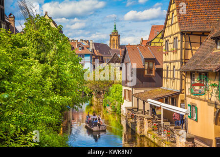 Historic town of Colmar, also known as Little Venice, with tourists taking a boat ride along traditional colorful - Stock Photo