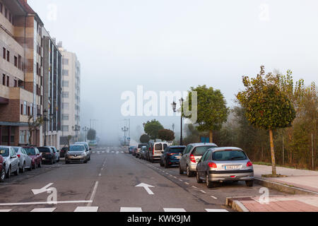 OVIEDO, SPAIN - OCTOBER 31, 2017: Cars parked along the road in Oviedo in the early morning with a thick morning - Stock Photo