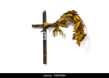 Wooden cross with a branch of laurel on the white wall - Stock Photo
