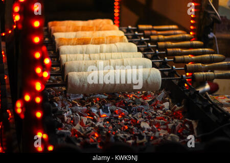 Kurtos kalacs (Chimney Cakes) baking on roll spinning over hot coals at a Christmas market stand - Stock Photo