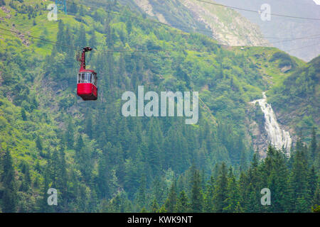 Cable car with green woods and Balea Cascada waterfall background in Sibiu, Romania - Stock Photo