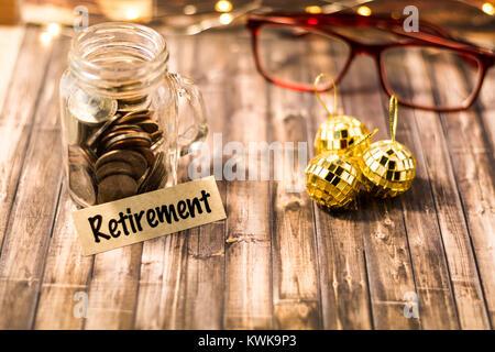 Retirement money jar savings motivational concept on wooden board - Stock Photo