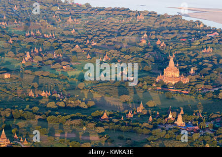 Aerial sunrise view flying over the temple and pagoda field at Bagan Myanmar as seen from a hot air balloon flight - Stock Photo