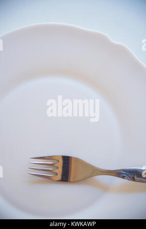 Fork on empty dish. - Stock Photo