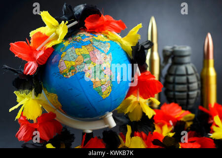 Globe with flower chain in German national colours, symbolic photo refugee's stream to Germany, Globus mit Blumenkette - Stock Photo