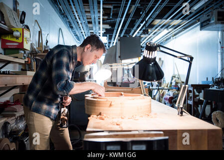 Side view of worker making guitar while standing in workshop - Stock Photo
