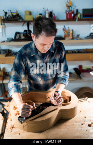 High angle view of man making guitar while working in workshop - Stock Photo