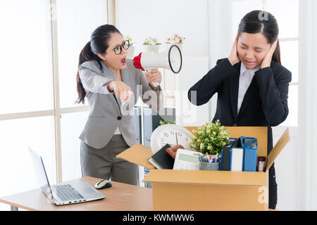 pretty attractive female boss speaking with young beauty girl business worker and using loudspeaker loudly shouting - Stock Photo