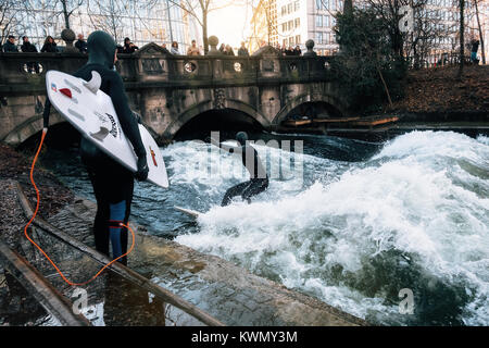 The surfer in diving suit wait their turn to ride the artificial wave on the Eisbach, dangerous water Isar river - Stock Photo