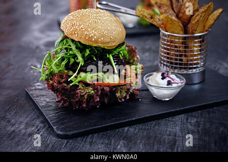 Burger, fries with salad on a table. - Stock Photo