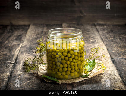Pickled green peas in glass jar. On a wooden background. - Stock Photo