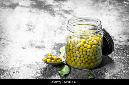Marinated green peas in glass jar. On a rustic background. - Stock Photo