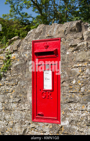 Red post Box built into the stone wall, Combrook, Warwickshire, England, UK - Stock Photo