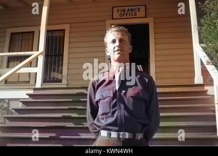 A young soldier in uniform stands at attention outside a military building with a sign reading 'Finance Office', - Stock Photo