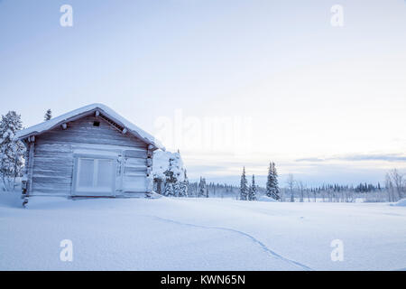 Old cottage, white winter in Scandinavia. Animal track in the deep snow. - Stock Photo