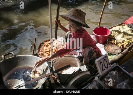 Thai woman frying and selling battered bananas from boat on river Damnoen Saduk Floating Market, Thailand. - Stock Photo