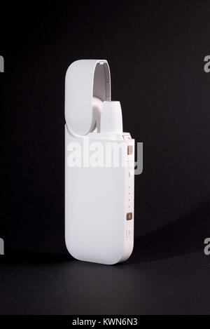 Newest electronic cigarettes, heating tobacco system IQOS, smoking, white isolated on black background - Stock Photo