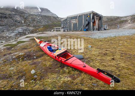 Sea kayaker using Texas Bar as shelter, old fur trapper cabin at Worsleyhamna, Liefdefjorden / Liefdefjord, Svalbard / Spitsbergen, Norway