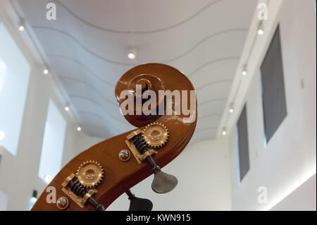 Neck head and scroll and tuning pegs of a hand carved double bass on view in the Museo del Violino, violin and string - Stock Photo