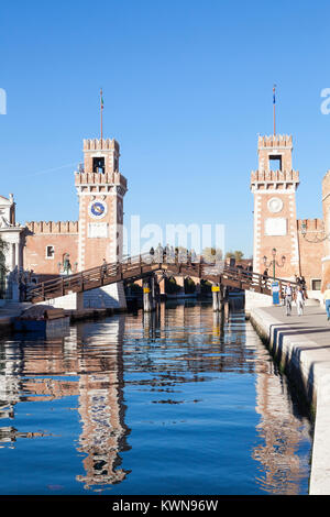 The entrance to the Arsenale, Castello, Venice, Italy reflected in Rio de l'Arsenal with tourists on Ponte de l'Arsenal - Stock Photo