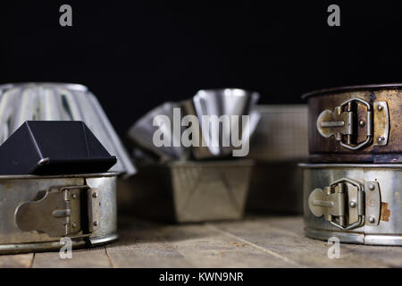 Tins and baking forms on a wooden table. Old kitchen accessories on the kitchen table. black background. - Stock Photo