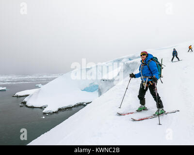 Alpine ski mountaineers skiing downhill in Antarctica - Stock Photo