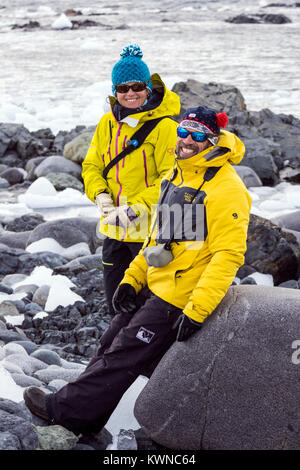 Two profesional mountain guides chat on rocky beach; Half Moon Island; Antarctica - Stock Photo