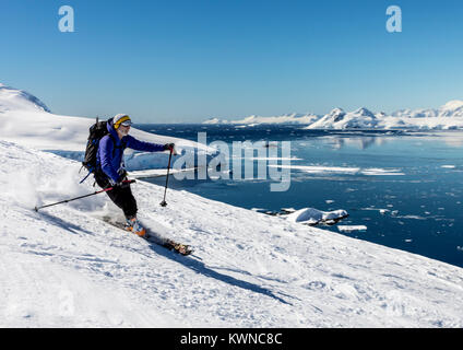 Alpine ski mountaineers skiing downhill; Nansen Island; Antarctica - Stock Photo