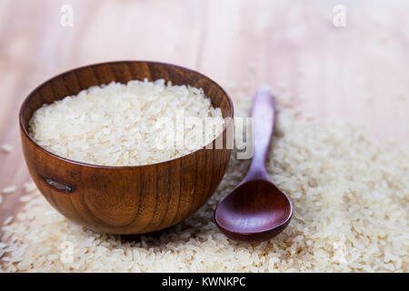 Raw long-grain steamed rice in a bowl on a wooden background. Ingredient for a healthy diet. - Stock Photo
