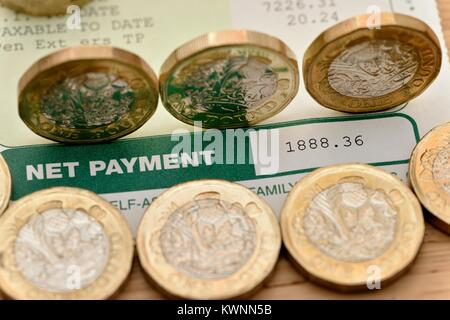 Net payment on a payslip with new one pound coins - Stock Photo