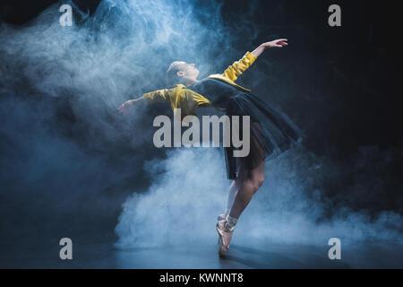 Girl dancing in smoke - Stock Photo