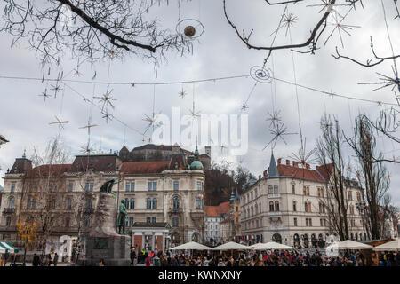 LJUBLJANA, SLOVENIA - DECEMBER 16, 2017: Crowd gathered for Christmas market on Presernov Square with Tromostovje - Stock Photo