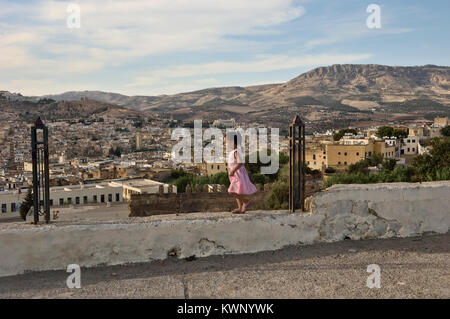 A child playing on a wall above the city of Fez, Morocco, North Africa - Stock Photo
