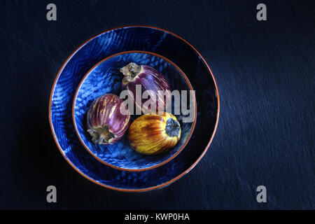 Healthy and fresh purple eggplants in a bwols over dark stone background. Vegetarian food, health or cooking concept, - Stock Photo