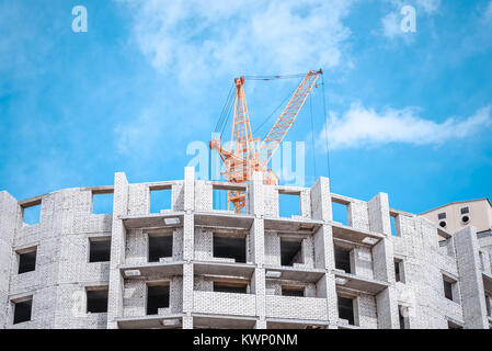 crane against sky building a new block of flats. new multi-storey house. Building crane and building under construction - Stock Photo