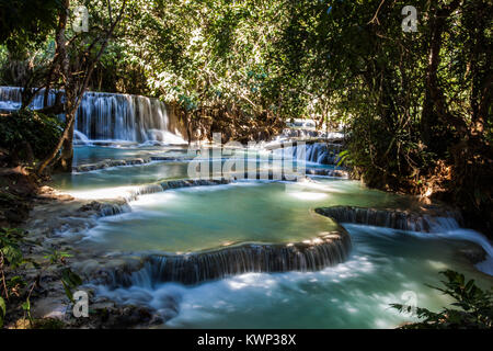 shallow waterfall situated in jungle with turquoise limestone water and jungle foliage surrounding. - Stock Photo