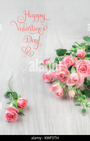 Small pink roses on wooden table, romantic greeting card, text 'Happy Valentine's Day'. This image is toned. - Stock Photo