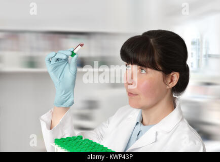 Female young doctor-intern, tech or a scientist with blood test tubes in medical or research facility - Stock Photo