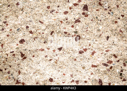 background texture close up of brown and tan crushed stonework on an exterior wall - Stock Photo