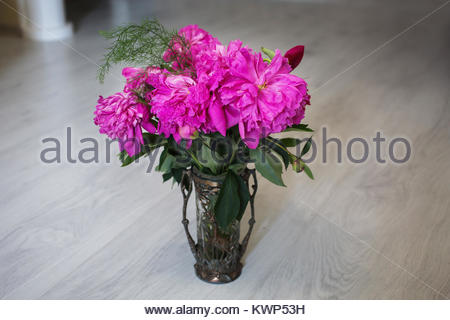 Bouquet of pink, purple flowers in a vintage vase stand on a light background. - Stock Photo