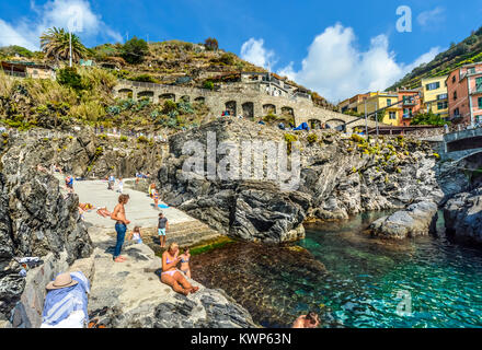 Tourists swim at the coastal harbor bay of the village of Manarola Italy, on a sunny day in Cinque Terre Italy - Stock Photo