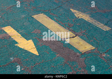 perspective view of yellow arrows painted on blue cracked asphalt bicycle track - Stock Photo