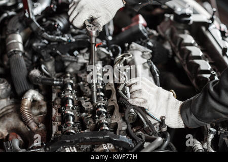 Repairing of modern diesel engine, workers hands and tool. Close-up of an auto mechanic working on a car motor - Stock Photo