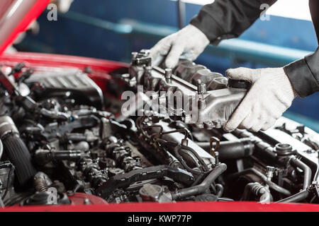 Repairing of modern diesel engine, workers hands and tool. Car mechanic looking at engine for analysis symptoms - Stock Photo