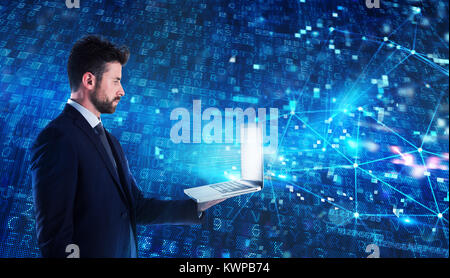 Programmer man works with a laptop on a network application - Stock Photo