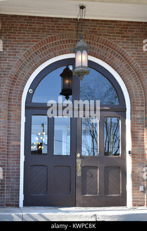 Old wooden doors with reflection of a tree in the glass - Stock Photo