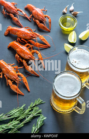Boiled crayfish with two mugs of beer - Stock Photo