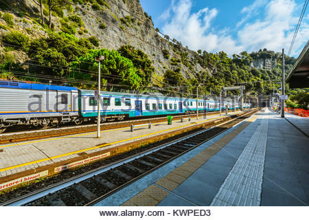 A moving Trenitalia train passes by the tracks at the railway station in the afternoon at Monterosso Al Mare, Cinque - Stock Photo
